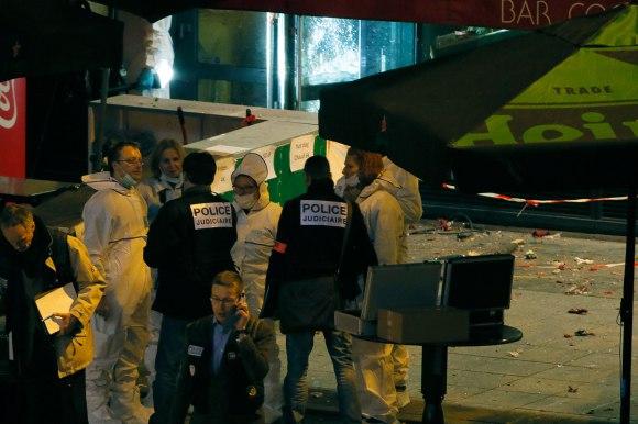 Para penyelidik bekerja di luar sebuah bar dekat Stade de France di mana ledakan dilaporkan terjadi pada waktu pertandingan sepakbola Prancis vs Jerman dekat Paris, 13 November 2015.  (REUTERS/Gonazlo Fuentes-RTS6W9G)