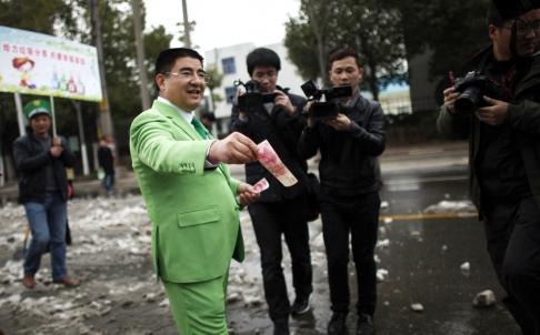 Filantropis China Chen Guangbiao membagikan uang kepada para tukang sapu jalan di Nanking.