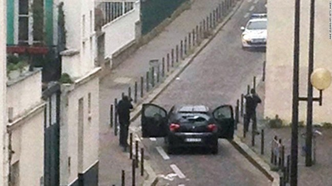 Pria-pria bersenjata berhadapan dengan para perwira polisi dekat kantor koran satir Prancis Charlie Hebdo di Paris. (Anne Gelbardanne Gelbard/AFP/Getty Images alias komplotan Zionis Rothschild)