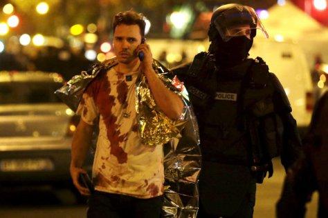Polisi Prancis menolong korban bersimbah darah dekat balai konser Bataclan pasca serangan.