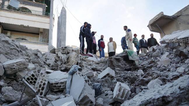 Para penduduk memeriksa lokasi yang rusak akibat, menurut para aktivis, serangan udara oleh AU Rusia di kota Nawa, Deraa, Suriah. [Reuters/Alaa Al-Faqir]